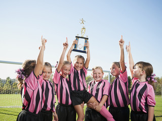 Cheering girl soccer players posing with trophy