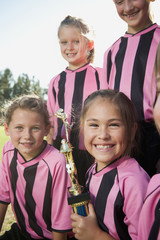 Smiling girl soccer players posing with trophy