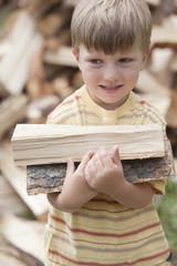 Caucasian boy carrying firewood