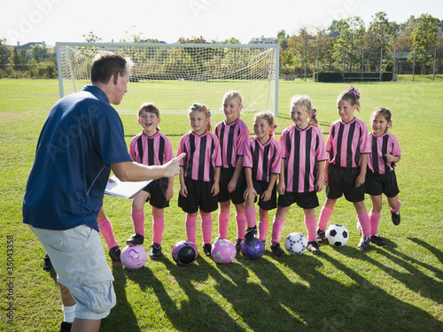 Coach motivating girl soccer players