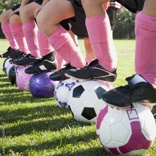 Girl soccer players standing with feet on soccer balls