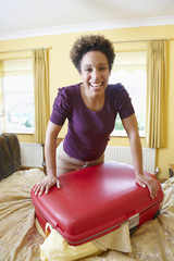 Mixed race woman closing suitcase
