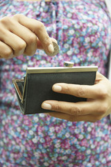 Mixed race woman putting coin in purse