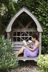 Mixed race woman reading book in backyard