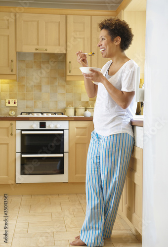 Mixed race woman eating cereal in kitchen