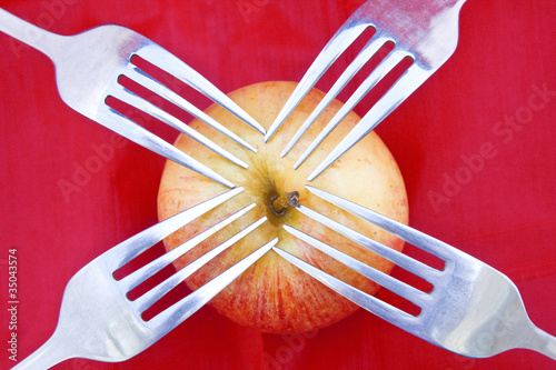 Red apple on red with four forks