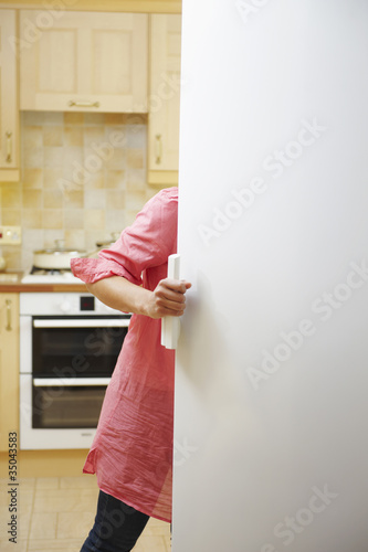 Mixed race woman opening cupboard in kitchen