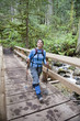 Hispanic woman hiking over bridge in woods