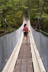 Hispanic woman hiking over bridge in woods