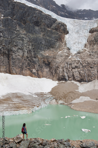 Hispanic woman hiking hear glacial lake