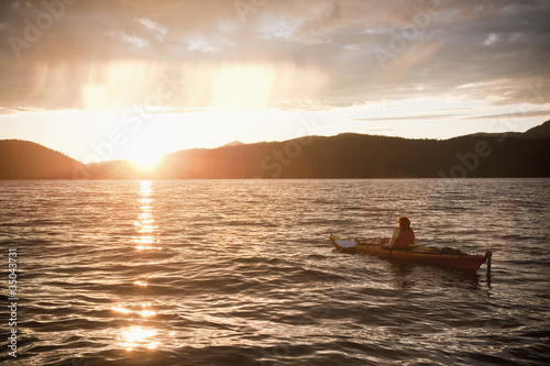 Hispanic woman kayaking on lake