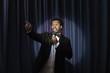 Black man in tuxedo holding microphone