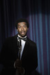 Smiling Black man in tuxedo standing at microphone