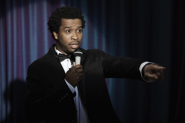 Serious Black man in tuxedo holding microphone
