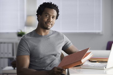 Serious Black man sitting at desk with book in home office