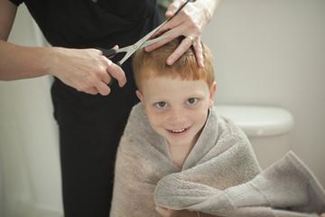 Caucasian mother giving son haircut