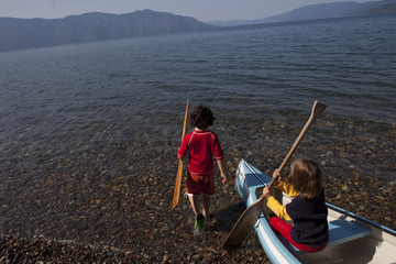 Caucasian children with canoe on shore of lake