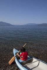 Caucasian boy sitting in canoe on shore of lake