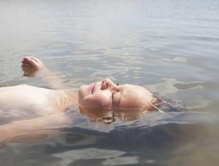 Caucasian boy floating in water