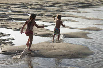 Caucasian brother and sister running through puddles on beach