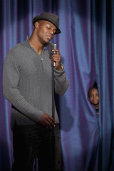 Black boy watching man singing into microphone