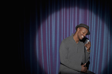 Smiling Black man singing into microphone