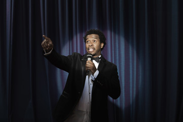Black man in tuxedo holding microphone