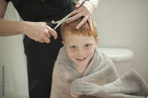 Caucasian mother giving son haircut