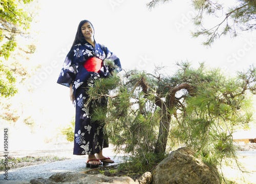 Mixed race woman in garden wearing Japanese kimono