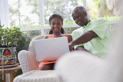 Black grandfather looking at laptop with granddaughter