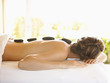 Rear view of woman lying on massage table receiving lastone therapy at a luxury spa in Napa Valley California