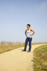 Mixed race woman resting after exercise on remote path