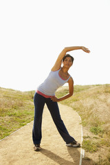 Mixed race woman stretching on remote path