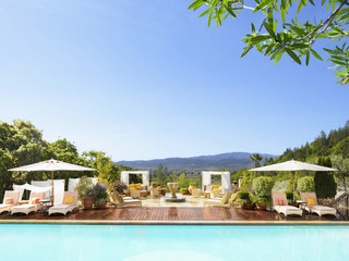 """Swimming pool with striped chaise lounge chairs and umbrellas at a luxury resort overlooking Napa Valley, California"""