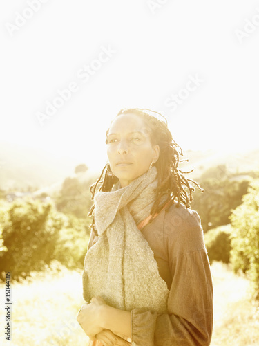 Close up portrait of beautiful African American woman with dreadlocks in nature