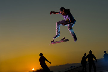 Caucasian skateboarder doing stunt in mid-air at sunset