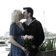 Caucasian woman holding bouquet and kissing boyfriend near Eiffel Tower