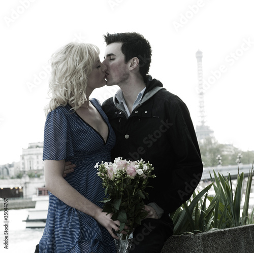 Caucasian woman holding bouquet and kissing boyfriend near Eiffel Tower