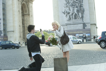 Caucasian man taking photograph of girlfriend near Arc de Triomphe