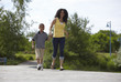 Black mother and son walking down road together