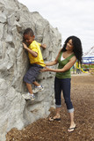 Black mother helping son climb rock wall