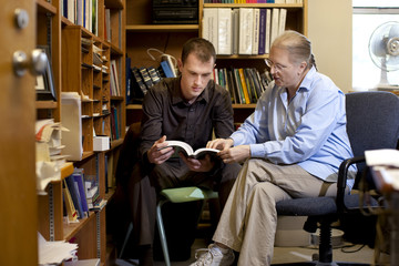 Teacher talking with student about book