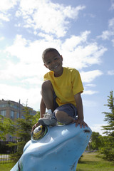 Black boy sitting on frog statue in park