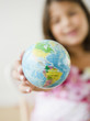 Hispanic girl holding small globe