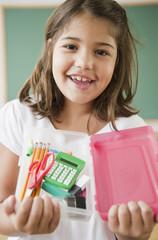 Hispanic girl holding school supplies