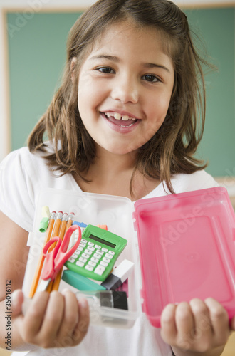 Hispanic girl holding school supplies