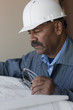 Hispanic worker in hard-hat looking at blueprints