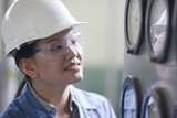 Chinese worker in hard-hat looking at gauges