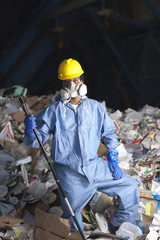 Black sanitation worker standing in garbage at recycling plant