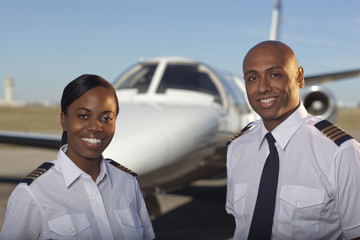 Pilots standing near private jet